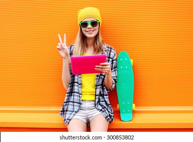 Fashion and technology concept - stylish pretty cool girl with digital tablet pc having fun in the city, wearing a sunglasses and casual colorful clothes