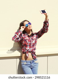 Fashion, technology and people concept - pretty girl wearing a sunglasses and checkered shirt makes self-portrait on the smartphone outdoors