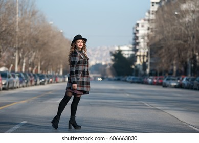 Fashion teen in city wear coat and hat walking in profile at the middle of the highway