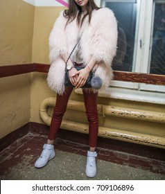 Fashion teen look style in pink fur coat advertise, red leather trousers and white shoes. Fashionable student girl wears leather pants, posing in corridor background.