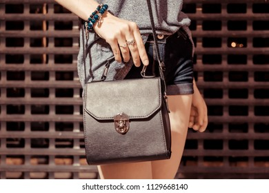 Fashion teenage woman standing in night city street in front of night club door, Stylish female model with black leather handbag, image with copyspace