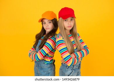 Fashion that matches their conscious style. Small girls in style keeping arms crossed on yellow background. Little children wearing baseball caps in casual streetwear style. Hip hop or hipster style.