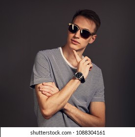 Fashion thinking man posing in trendy sunglasses with finger under the face and watch o the hand in strip casual shirt on grey background. Toned closeup portrait