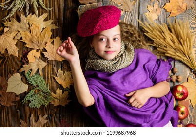 Fashion trend fall season. Child lay wooden background fallen leaves top view. Knitted accessory fashion detail. Fashion kid girl wear knitted hat beret and scarf. Autumn fashion accessories concept.