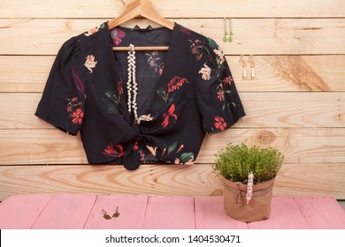 Fashion trends - black crop top / blouse in floral print on hangs on hanger and jewelry: hair pearl clip, necklace, earrings on wooden background