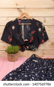 Fashion trends - black crop top / blouse in floral print on hangs on hanger, blue skirt, belt and jewelry: hair pearl clip, necklace, earrings on wooden background. vertical photo