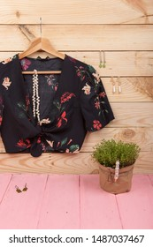 Fashion trends - black crop top / blouse in floral print on hangs on hanger and jewelry: hair pearl clip, earrings on wooden background. vertical photo