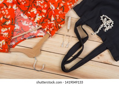 Fashion trends - black eco tote bag, dress in floral print on hanger and pearl jewelry: necklace, hair pearl clip, earrings on wooden desk