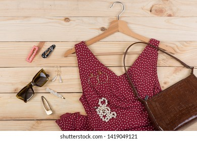 Fashion trends - sunglasses, bag, red dress in polka dots on hanger and jewelry: pearl necklace, hair pearl clip, earrings on wooden desk