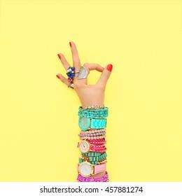 Fashion. Trendy wrist watches, jewelry, female hand, OK gesture, accessories set. Minimal design. Stylish summer fashionable woman. Creative art shopping concept on yellow, summertime