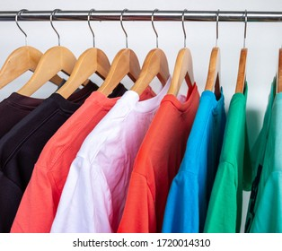 Fashion T-shirt on clothing rack - Closeup of bright colorful closet on wooden hangers in store closet