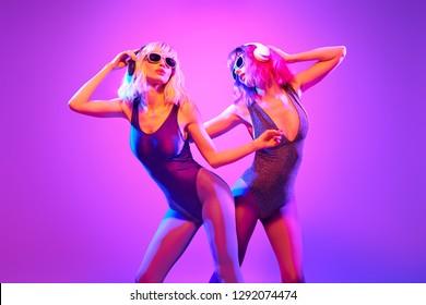 Fashion. Two DJ girl in Colorful neon light enjoy music, friends. Party disco 80s 90s neon nightclub vibes. Model woman in disco bodysuit, makeup dance. Creative art neon light