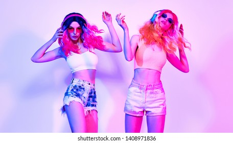 Fashion. Two DJ girl in Colorful neon light, friends. Party disco neon nightclub music vibes. Model woman with trendy fashionable hair, makeup dance. Creative art neon summer party light