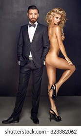 Fashion type portrait of an elegant man and naked woman