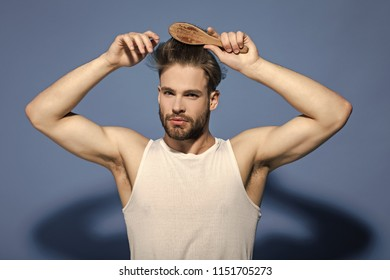 Fashion, underwear, style. Man brush hair with hairbrush on blue background. Haircare, hairstyle concept. Beauty, grooming, hygiene. Macho with bearded face and haircut in white singlet.