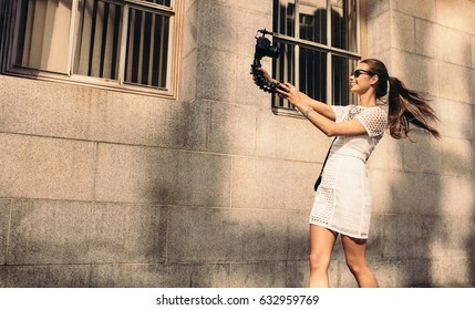 Fashion vlogger recording content for her vlog. Young woman taking selfie in a street using a digital camera on flexible tripod.