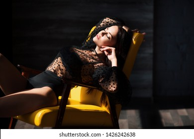 Fashion vogue style portrait of young stunning woman posing in sunset lightning with shadows in dark interior. Gorgeous glamorous brunette girl with perfect breast