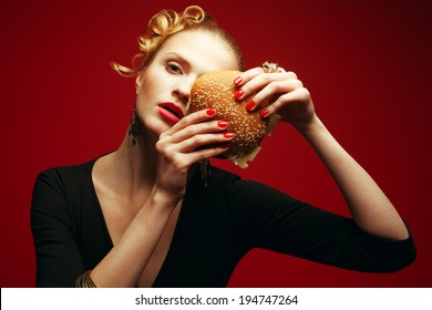 Fashion vs Junk Food Concept. Guilty pleasure. Fashionable model holding burger near face over red background. Perfect hair, skin, make-up & manicure. Golden accessories. Close up. Studio shot