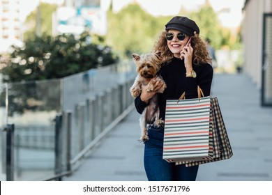 Fashion walk woman with long curly hair holds small dog and shopping bags. Beautiful girl hugs little dog. Smiling attractive woman with Yorkshire terrier. Girl with dog in hands, and sale concept.
