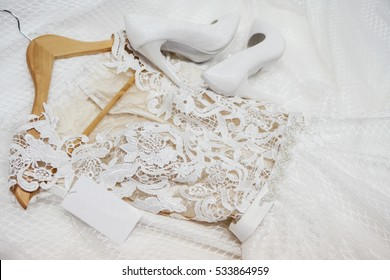 Fashion wedding dress is on a hanger with tag and white bridal shoes. View from above. Clothes for bride. Fashion look.