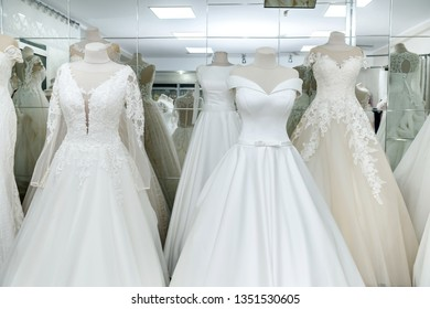 Fashion wedding dresses on hanger and mannequins in salon