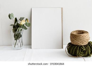 Escena de simulación de la papelería de bodas de moda. Una tarjeta vertical de saludo vacía y flores blancas secas sobre un fondo de lino blanco. La vida femenina, vista de arriba.