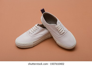 fashion white trendy sport shoes or sneakers on brown background