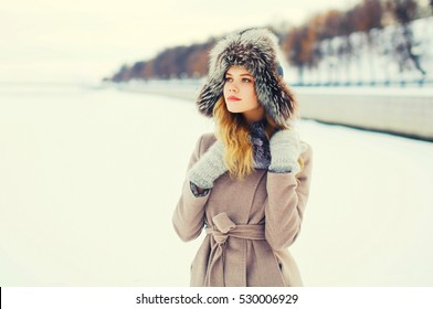 Fashion winter portrait beautiful young woman wearing a coat jacket and hat over snow