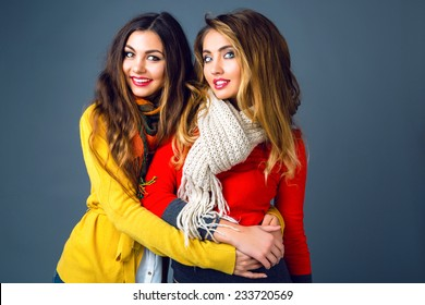 Fashion winter portrait of blonde and brunette beautiful best friends girls, hugs and having fun. Wearing bright stylish cashmere sweaters and scarfs. Have trendy make up and long amazing hairs.