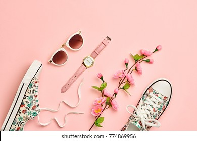 Fashion Woman Accessories summertime Set. Coral Pastel Color. Flat lay. Minimal Style. Trendy Sneakers, fashionable Summer Sunglasses. Blossom Flowers. Spring Floral