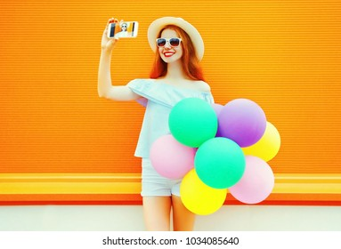 Fashion woman with an air colorful balloons takes a picture self portrait on a smartphone on orange background