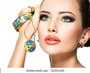 Fashion woman with beautiful art jewelry.  Portrait of a pretty  girl with creative make-up