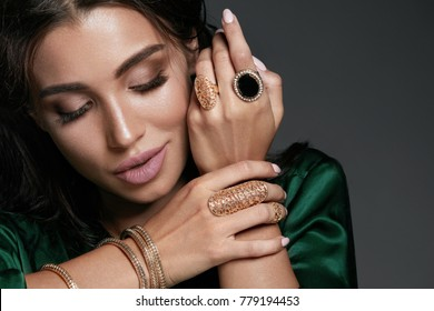 Fashion Woman. Beautiful Female With Jewelry. Portrait Of Glamourous Sexy Woman With Professional Face Makeup Wearing Luxury Gold Bangles And Rings. Beauty And Accessories. High Quality Image.