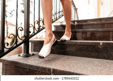 Fashion woman with beautiful legs in stylish summer leather sandals comes down the stairs in city. Close-up.