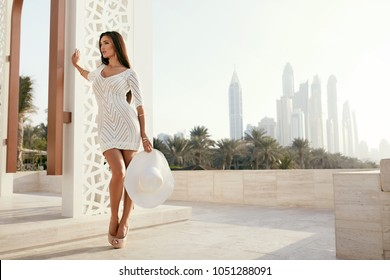 Fashion. Woman In Beautiful White Dress Outdoors On Street. Portrait Of Sexy Young Female Model Wearing Stylish Clothes Holding White Fashionable Hat At Luxury Resort In Summer. High Resolution.