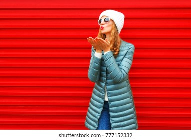 Fashion woman is blowing red lips sends an air kiss on a background