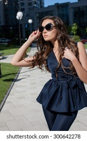 Fashion  woman in a blue suit, her face wearing sunglasses, she looks in profile
