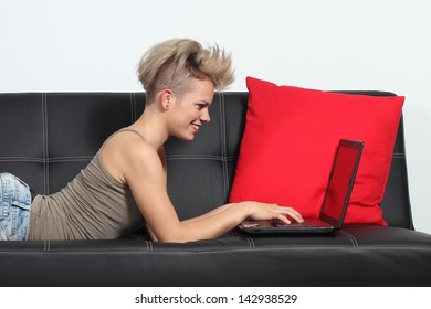 Fashion woman browsing internet in a laptop at home lying on a black couch
