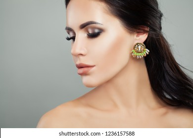Fashion woman. Brunette lady with makeup and earrings