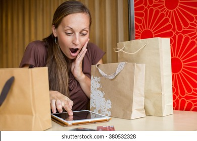 Fashion woman buying online with smart phone and credit card with craft shopping bags beside