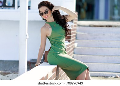 Fashion woman in casual green dress posing at urban street background. Fashionable brunette girl model in elegant fitting dress outdoors.