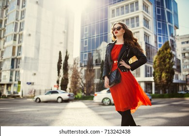 Fashion woman in casual red dress and black leather jacket on urban city background autumn portrait. Fashionable long hair model walking on street at sunset. Casual fashion and elegant look lady.