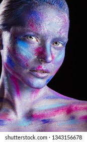 Fashion woman with colorful make-up and body art on a black background