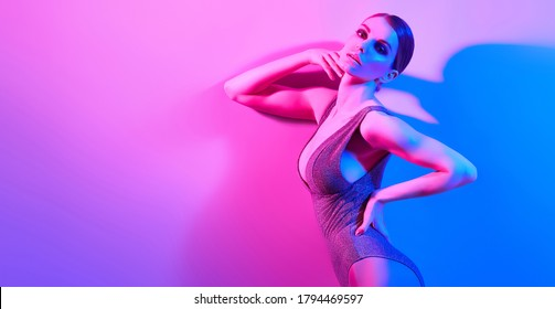 Fashion. Woman in colorful neon light, make-up. Sexy girl, stylish hair, trendy bodysuit, makeup. Party disco neon style. Creative art beauty concept, fashionable fitness model, bright color