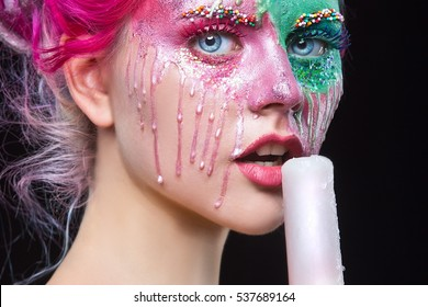 Fashion woman with creative make up eating ice cream. Young woman with pink dreads. Bizarre pink hair girl. Creative make up.  Halloween.