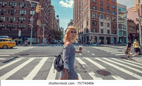 Fashion woman crossing the street in New York, with a cup of coffee