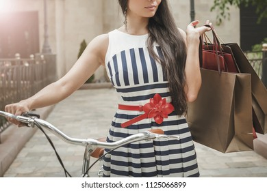 Fashion woman dressed in striped dress with bags and vintage bike has shopping travel to Italy, Milan. Shoping. Wuman has happy vacation travel to Europe