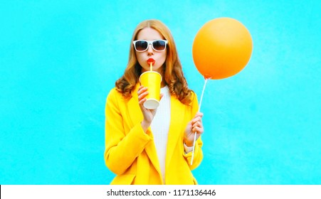 Fashion woman drinks fruit juice holds an orange air balloon on colorful blue background