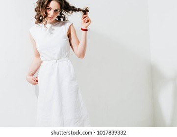 Fashion woman with freckles face, curly hair in white dress on white background