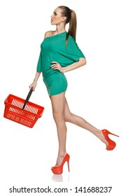 Fashion woman in full length wearing green dress and high heels red shoes walking with empty shopping basket. Isolated on white background